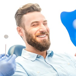 A young male with a beard smiling at himself in the mirror while in the dentist's chair