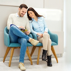 A couple waiting in the dentist's office lobby, smiling while reading a magazine