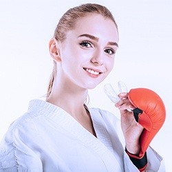 Teen girl with boxing gloves placing athletic mouthguard