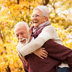 An older man and woman smiling and having fun outside after receiving their dentures