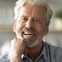 An older man smiling and showing off his customized dentures after enrolling in flexible financing to be able to afford them