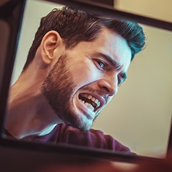 Man looking at his smile in mirror