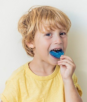 Young boy placing mouthguard