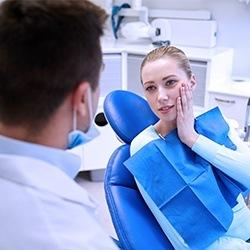 Woman in dental exam room holding cheek