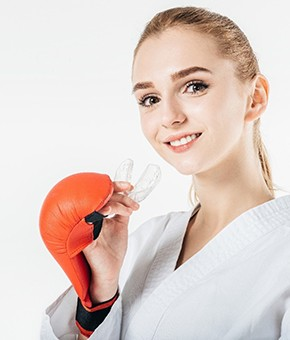 A young woman wearing a boxing robe and gloves and preparing to insert her mouthguard