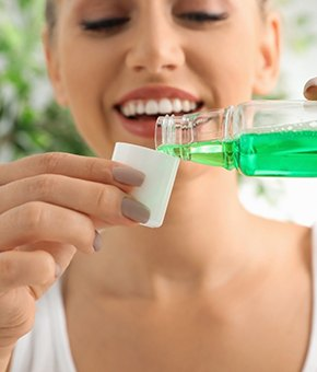 A woman pouring 20 ml of mouthwash into a cup and preparing to rinse out her mouth