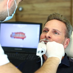 A dentist in Garland using an iTero Element Scanner inside a male patient's mouth