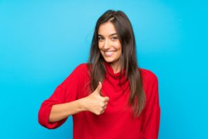 a woman smiling and giving a thumbs up