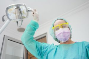 a dental staff member wearing personal protective equipment while adjusting the overhead light